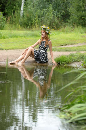 girl in a wreath of flowers near the water photo