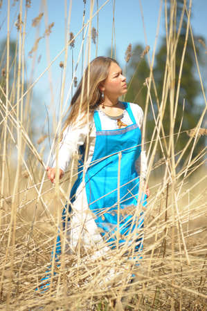 girl in a blue sundress in a field of tall dry grass Stock Photo - 15384413