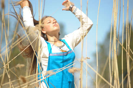 girl in a blue sundress in a field of tall dry grass photo