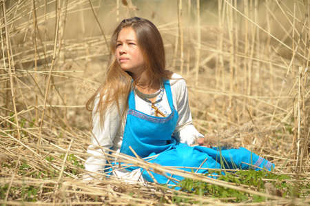 child girl nude: girl in a blue sundress in a field of tall dry grass