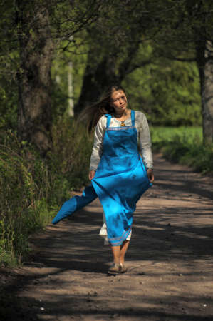 girl goes on a path in a park sundress photo