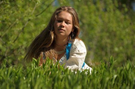 Young woman lying on the green grass photo