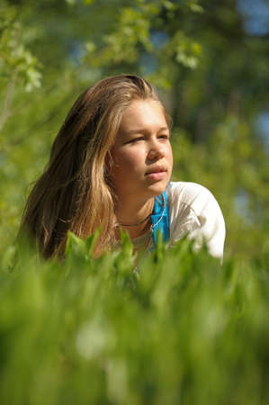 Young woman lying on the green grass Stock Photo - 15018459