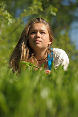 Young woman lying on the green grass Stock Photo - 15018458