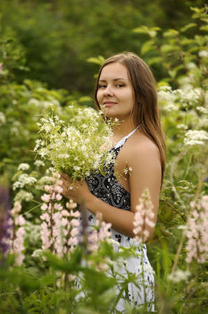 Portrait of a young woman on flowers field photo