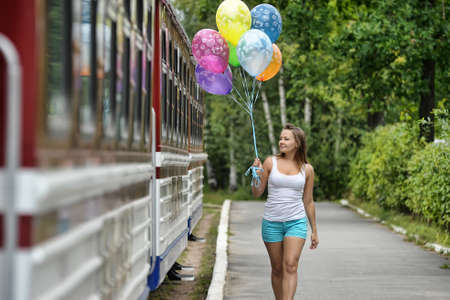ni�a con globos y trenes photo