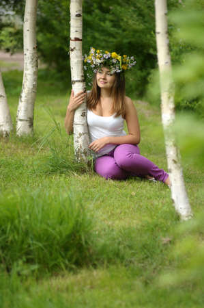 beautiful young woman in a wreath of flowers near the birch photo