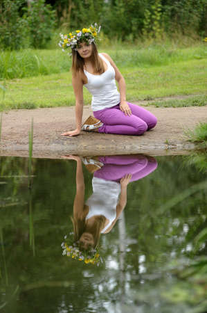 Girl sitting near lake and look at the water photo