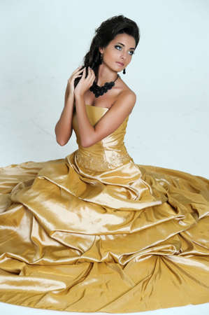 view of a beautiful woman in golden dress photo