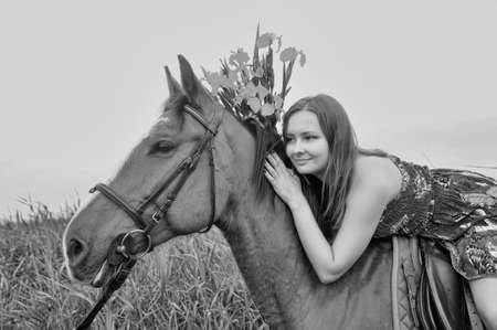 Young girl in dress with  horse photo