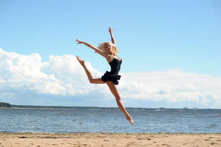Happy healthy woman leaping on seashore on summer vacation Stock Photo - 14999985