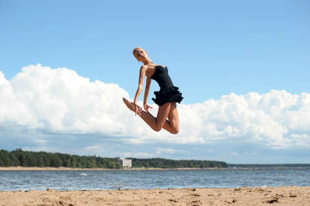 Happy healthy woman leaping on seashore on summer vacation Stock Photo - 14999982