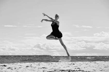 Happy healthy woman leaping on seashore on summer vacation photo