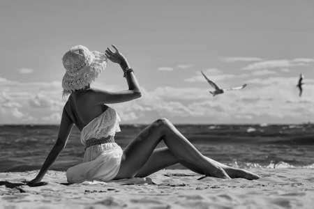 pin up vintage: la ragazza in un vestito e cappello sulla spiaggia Archivio Fotografico