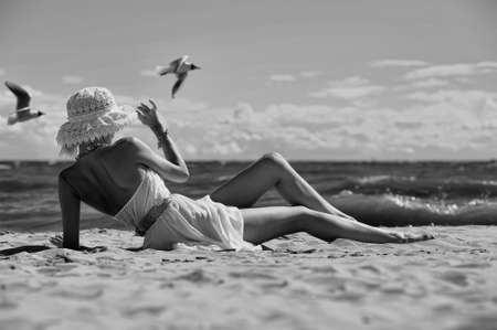 pin up vintage: la ragazza in un abito e cappello sulla spiaggia