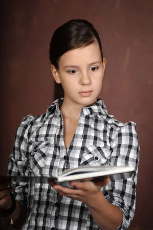 girl with astonishment looks in the book photo