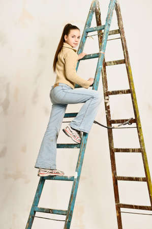 The teenager the girl rises on a step-ladder photo