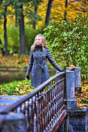girl in autumn park walking across the bridge photo