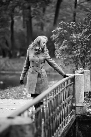 girl in autumn park walking across the bridge photo