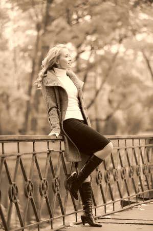 wide wet: girl in autumn park walking across the bridge