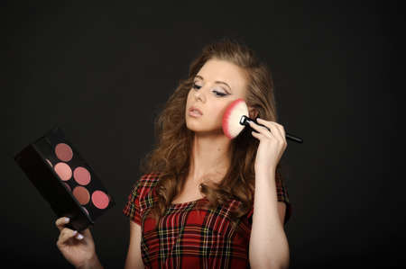 Charming woman is doing make-up photo