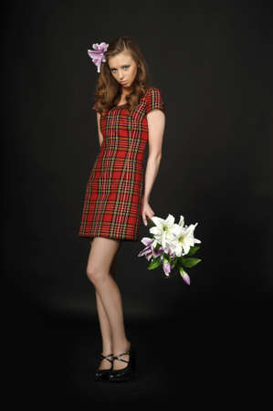 girl in a plaid dress with a bouquet of lilies photo
