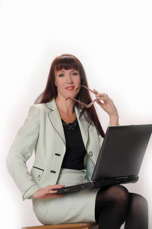 Assertive woman with glasses working on laptop  photo