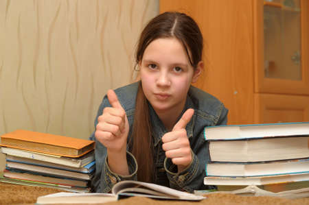 Happy smiling teenage girl studying with books photo