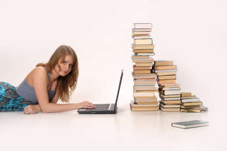 girl with a laptop next to a pile of books photo