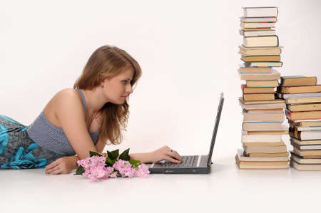 modern generation: girl with a laptop next to a pile of books