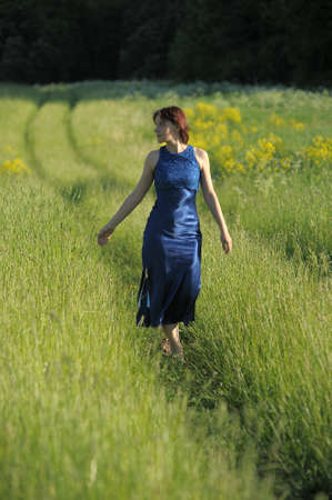 young woman in a blue dress in a grass field Zdjęcie Seryjne