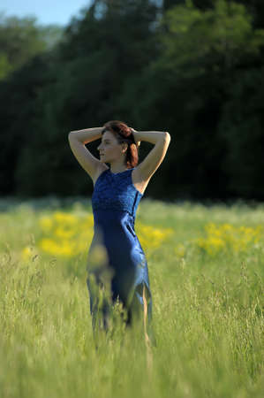 young woman in a blue dress in a grass field Stock Photo - 17108613
