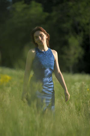 young woman in a blue dress in a grass field photo
