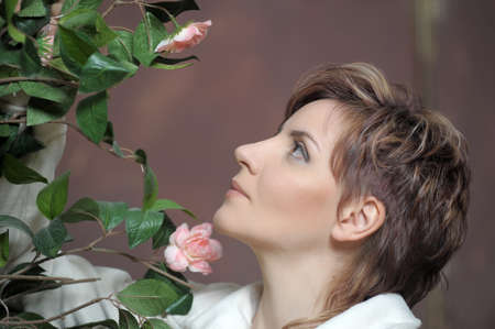 young elegant woman next to a bush of roses photo
