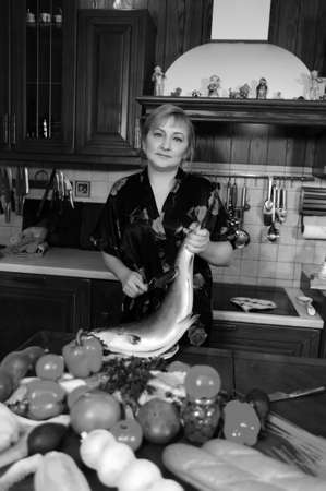 The woman fish at itself on kitchen photo