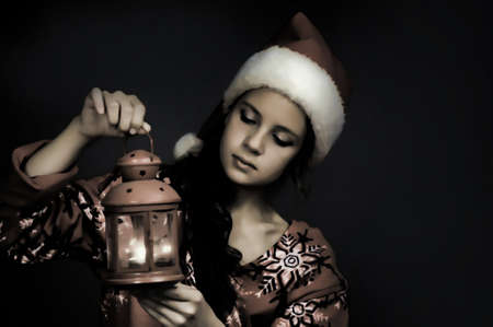 Girl in santa hat with Christmas lantern photo