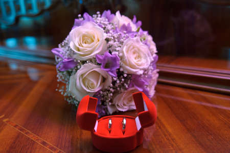 bridal bouquet and wedding rings in a box photo