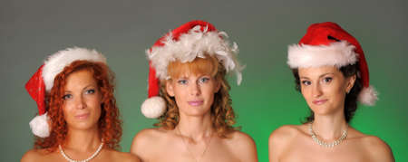 Three girls in Christmas hats on a green background photo