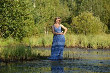 beautiful young woman in sundress near the lake photo
