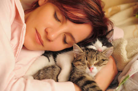 beautiful young woman sleeps with cats photo