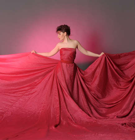 The beautiful girl in a long red dress  Stock Photo - 15356218