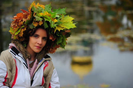 Girl in a wreath from autumn leaves photo