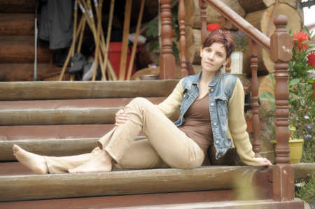 girl sitting on the wooden steps of the house photo