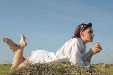 Pretty girl  on haystack in field photo