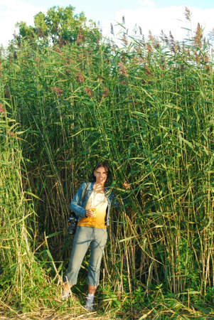 girl stands among the very tall grass photo