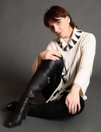 young woman in a sweater and boots photo