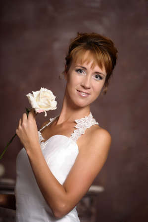 woman in a white dress with a white rose photo