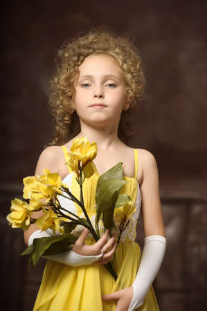 Girl in a yellow dress with a flower in hand photo