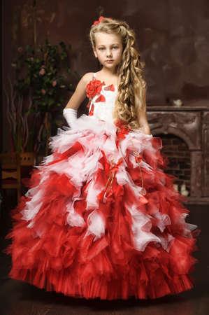 Blond meisje in een slimme witte met een rode jurk
