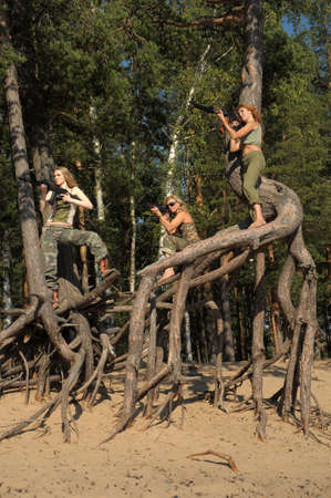 Four girls in armed ambush on a tree Stock Photo - 21997227
